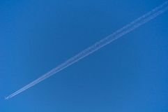 Diagonalny samolotowy ślad na jasnym niebieskim niebie Zdjęcia Stock