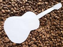 diagram av en akustisk gitarr i vit och bakgrund med grillade kaffebönor arkivbilder