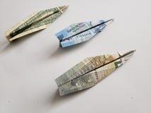 diagram av ett pappers- flygplan gjorde med en dollarräkning, en mexikansk sedel av 20 pesos och en anmärkning av euro fem arkivfoton