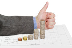 Diagram, built of coins on the background of approving gesture Stock Photos