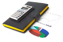 Diagram and calculator. Calculator on a diagram with some graphs and data royalty free stock photography