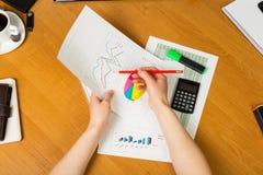 Diagram, grafer och blyertspenna i händer man, räknemaskin, på skrivbordet Royaltyfria Foton