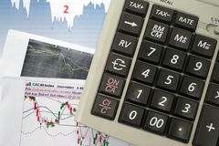 Diagram grafer, räknemaskin Mäklarehjälpmedel som analyserar aktiemarknaden och som tar det högra beslutet arkivfoto