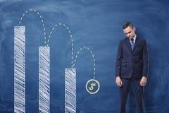Diagrama del trastorno y de columna de la situación del hombre de negocios con una muestra de dólar que cae abajo Imagen de archivo