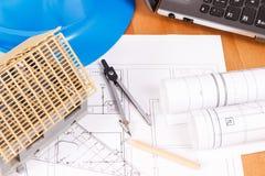 Diagramas bondes, acessórios para trabalhos do coordenador e casa sob a construção na mesa, conceito home de construção Fotografia de Stock
