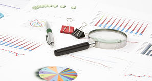 Diagramas de la aún-vida del negocio, lupa, pluma, paperclip Foto de archivo libre de regalías