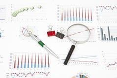 Diagramas de la aún-vida del negocio, lupa, pluma, paperclip Imágenes de archivo libres de regalías
