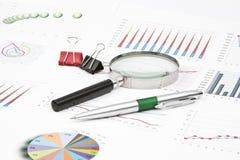 Diagramas de la aún-vida del negocio, lupa, pluma, paperclip Fotografía de archivo libre de regalías