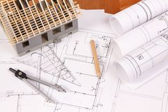 Diagramas eléctricos, accesorios para los trabajos del ingeniero y casa bajo construcción en el escritorio, concepto casero const Fotos de archivo