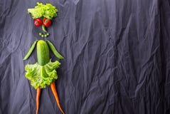 Diagramet av flickan med grönsaker på svart pappers- bakgrund Viktförlust och sund livsstil arkivfoton