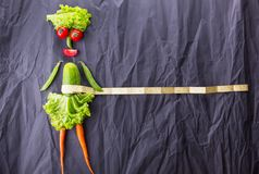 Diagramet av flickan med grönsaker på svart pappers- bakgrund Viktförlust och sund livsstil Med avstånd för text fotografering för bildbyråer