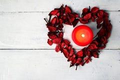 Diagramet i form av hjärta och en röd stearinljus på en vit bakgrund Arkivfoton