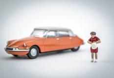 Diagramet miniatyr en kvinna har precis parkerat dess orange bil royaltyfri bild