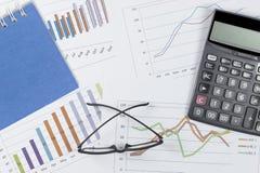 Diagramm mit Notizbuch, Gläsern und Taschenrechner auf Börsenbericht als Hintergrund Lizenzfreie Stockfotos