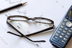 Diagramma di riserva con una matita, un telefono ed i vetri Immagini Stock Libere da Diritti