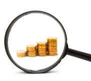 The diagramme from coins and a magnifier. Stock Photography