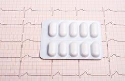 Diagramme d'électrocardiogramme avec des pilules Photographie stock