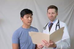 Diagramme de examen de médecin caucasien avec le patient asiatique Photo libre de droits