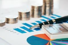Diagramme financier avec les pièces de monnaie, le stylo et la calculatrice Images libres de droits