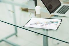 Diagramme, stylo et carnet financiers sur le lieu de travail des affaires Photos stock