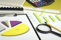 Diagrammes, livres de comptes, calculatrice et loupe sur la table en bois de bureau Concept financier et de budget image libre de droits