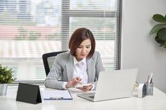 Diagrammes travaillants asiatiques de données de discussion et d'analyse de graphe par point de femme d'affaires ou de comptable  photo libre de droits