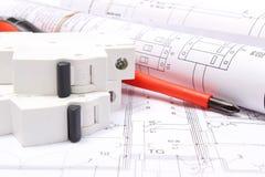 Diagrammi elettrici rotolati, fusibile elettrico e strumenti del lavoro sul disegno di costruzione della casa Fotografia Stock Libera da Diritti