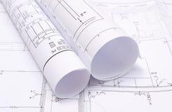 Diagrammi elettrici rotolati sul disegno di costruzione della casa Fotografia Stock Libera da Diritti