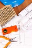 Diagrammi elettrici, strumenti arancio del lavoro, casco blu per i lavori dell'ingegnere e casa in costruzione, sviluppanti conce Immagine Stock