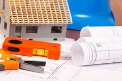 Diagrammi elettrici, strumenti del lavoro, casco per i lavori dell'ingegnere e casa in costruzione, sviluppanti concetto domestic Fotografie Stock Libere da Diritti