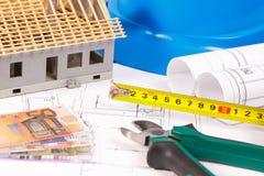 Diagrammi elettrici, strumenti del lavoro per i lavori dell'ingegnere, casa del giocattolo in costruzione e euro di valute, conce Fotografia Stock Libera da Diritti