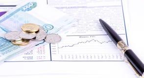 Diagrammi, penna, banconote e monete immagini stock libere da diritti