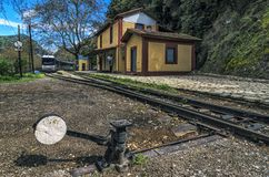 Diakopto - Kalavrita route Odontotos rack railway. Mega Spileon train station in Zachlorou village, Peloponnese - Greece. Odontotos train is arriving at the royalty free stock image