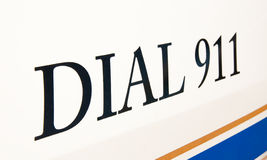 Dial 911 text on side of a police car. With a blue and a gold stripe Royalty Free Stock Images
