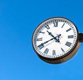 Dial de reloj con los números romanos aislado en fondo azul Imagen de archivo libre de regalías