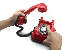 Dial de teléfono rojo viejo con las manos Imagen de archivo libre de regalías