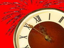Dial of hours and fireworks on red background.Eve of new year. Dial of hours taken closeup and fireworks on red background.Eve of new year Stock Photos