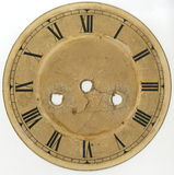 The dial of the old clock with Roman numerals and without arrows, with holes for the mechanism and keys of plant and translation. Yellowed, worn, cracked, with Stock Images