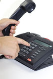 Dial a phone number with telephone. A man hand is dialing a telepone Royalty Free Stock Photography
