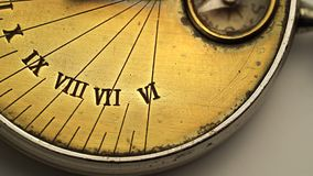 Dial of a sundial spinning on a white background. Close up. Dial of a sundial spinning on a white background and showing the exact time. Close up stock video footage
