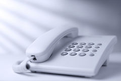 Dial up landline or terrestrial telephone. Low angle view of a white office dial up landline or terrestrial telephone with handset and keypad for telephonic Royalty Free Stock Images