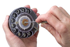 Dialer and hand with screwdriver. A rotary dial is a component of a telephone or a telephone switchboard that implements a signaling technology in royalty free stock photos
