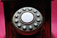 The dialer on an old telephone. With a pink background stock images