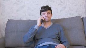 Diales del hombre un número en un teléfono móvil y las esperas una respuesta que se sientan en el sofá metrajes