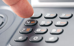 Dialing. A finger dialing on a phone keypad Royalty Free Stock Image