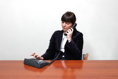 Dialing business woman. Adult white and young smiling female in a smart black jacket and a white blose who is talking on the phone at work and sitting behind a royalty free stock photography