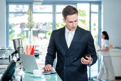 Dialing. Confident and successful businessman standing in an off Royalty Free Stock Image