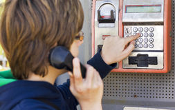 Dialing number on phone. Boy dials a phone number on a pay phone royalty free stock images