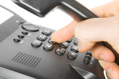 Dialing on phone. Finger and keypad. dialing on black telephone Royalty Free Stock Image