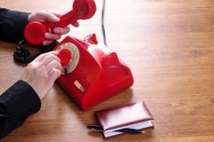 Dialing a phone number on retro telephone. Dialing a phone number on red retro rotary telephone to call on stock photography